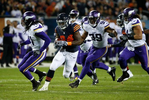 Chicago Bears running back Jordan Howard (24) runs from Minnesota Vikings strong safety Anthony Harris, from left, Danielle Hunter (99) and Eric Kendricks (54) during the first half of an NFL football game in Chicago, Monday, Oct. 31.