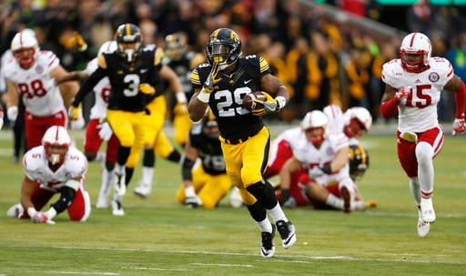 Iowa running back LeShun Daniels Jr. (29) runs from Nebraska linebacker Michael Rose-Ivey (15) during a 56-yard run in the first half of an NCAA college football game, Friday, Nov. 25, 2016, in Iowa City, Iowa.