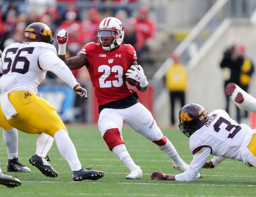 Wisconsin running back Dare Ogunbowale (23) scrambles between Minnesota linebacker Nick Rallis (56) and defensive back KiAnte Hardin (3) during the first half of an NCAA college football game Saturday, Nov. 26, 2016, in Madison, Wis.