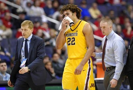 Minnesota center Reggie Lynch (22) is escorted to the bench after he took an elbow to the mouth during the second half of an NCAA college basketball game in the Big Ten tournament against Michigan State, Friday, March 10, 2017, in Washington.