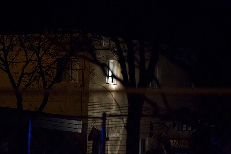 Police shine a spotlight on a window where a suspect in a shooting earlier today is in a standoff with police.