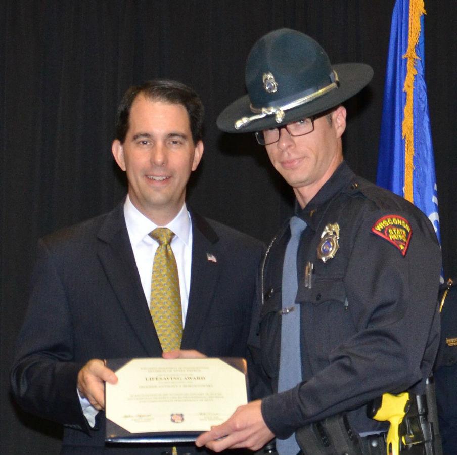 Gov. Scott Walker giving Trooper Anthony Borostowski the WSP's Lifesaving Award in 2015. WI DOT photo
