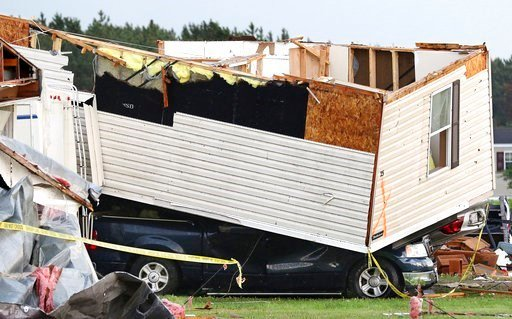 (Dan Reiland/The Eau Claire Leader-Telegram via AP). Part of a building sits on a vehicle after a tornado ripped through Prairie Lake Estates trailer home park, just north of Chetek, Wis., Tuesday, May 16, 2017.