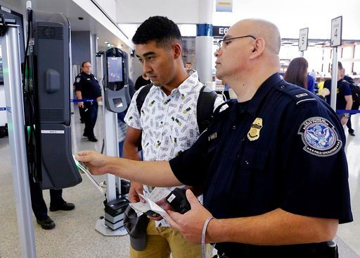 (Michael Wyke/Houston Chronicle via AP). In a June 29, 2017, photo, U.S. Customs and Border Protection Officer Sanan Jackson, right, helps a passenger navigate the new face recognition kiosks.
