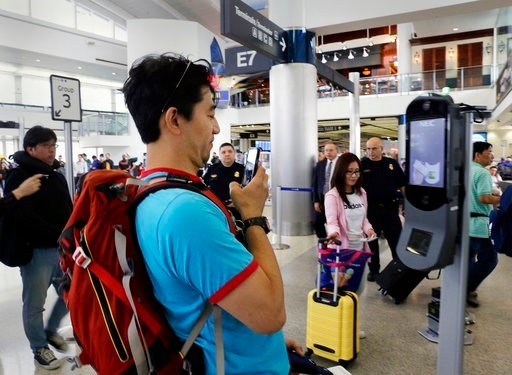 (Michael Wyke/Houston Chronicle via AP). In a June 29, 2017, photo, passenger Naoki Iseki takes a picture of one of the new face recognition kiosks at gate E7 before he boards a United Airlines flight to Tokyo.