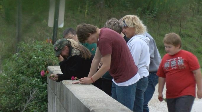 Lorenz's family throw flowers from the bridge where he was swept away ten years ago.