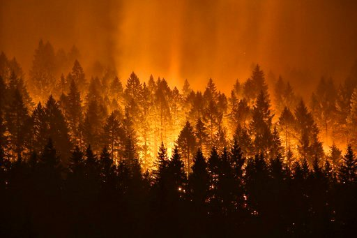(Genna Martin /seattlepi.com via AP). FILE - In this Sept. 5, 2017, file photo, the Eagle Creek wildfire burns on the Oregon side of the Columbia River Gorge near Cascade Locks, Ore.