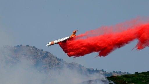 (AP Photo/Rick Bowmer). A heavy tanker drops retardant on a wildfire in Weber Canyon, Tuesday, Sept. 5, 2017, near Ogden, Utah.