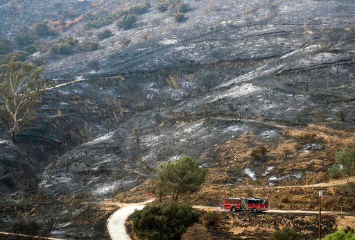 (AP Photo/Ringo H.W. Chiu). A fire engine drives past a burned area from a wildfire Monday, Sept. 4, 2017, in the Sunland-Tujunga section of Los Angeles.