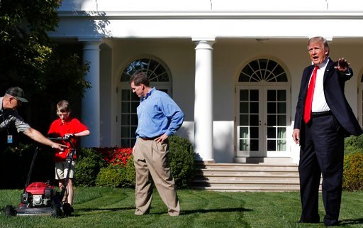 (AP Photo/Jacquelyn Martin). Frank Giaccio, 11, of Falls Church, Va., left, is assisted by a member of the National Park Service, and his father Greg Giaccio, as he gets back to mowing the lawn after President Donald Trump said goodbye.