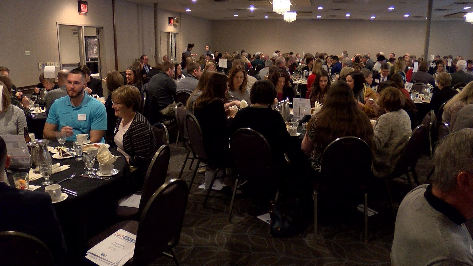 Crowd eats while waiting for annual meeting to begin.
