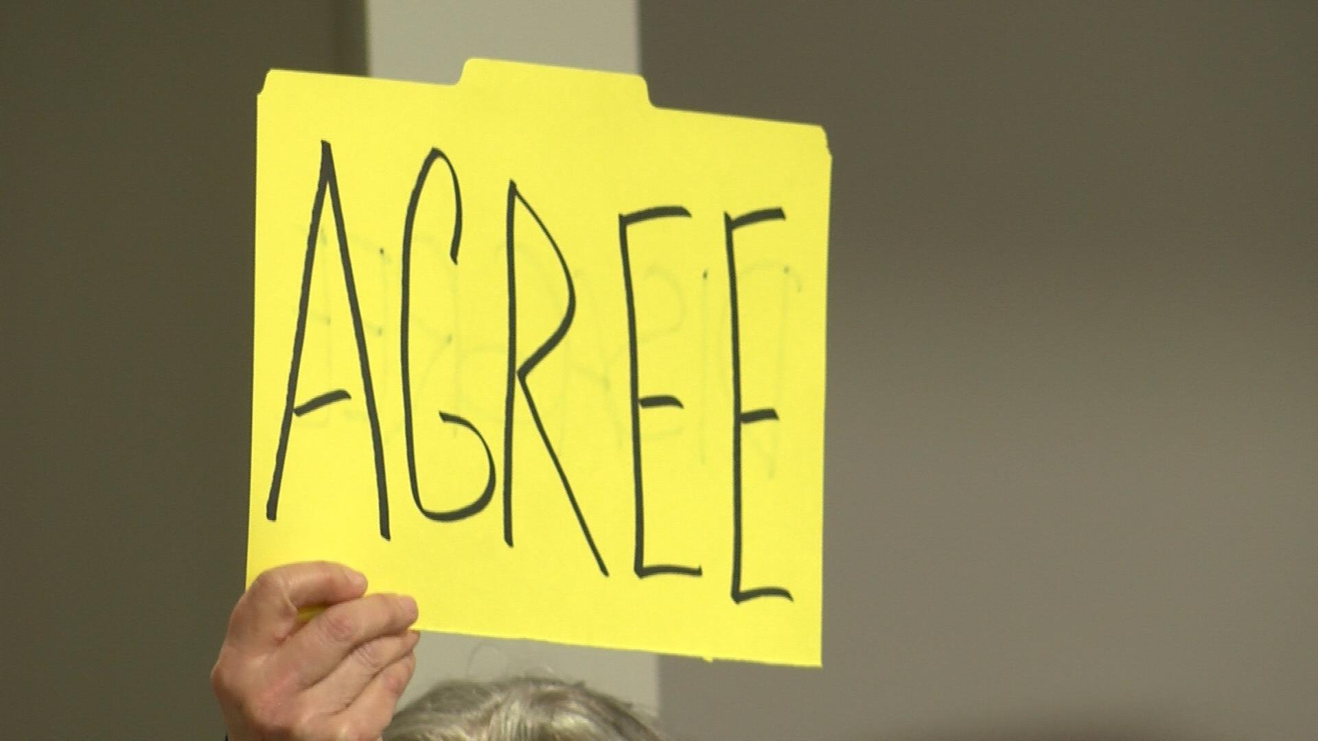 """Attendee holds up sign reading """"agree""""."""