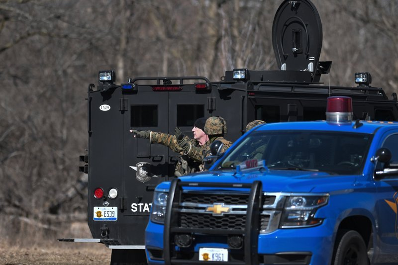 Officers search a wooded area for a suspect involved in a shooting at a Central Michigan University residence hall on Friday, March 2, 2018 in Mt. Pleasant, Mich.  (Matthew Dae Smith/Lansing State Journal via AP)