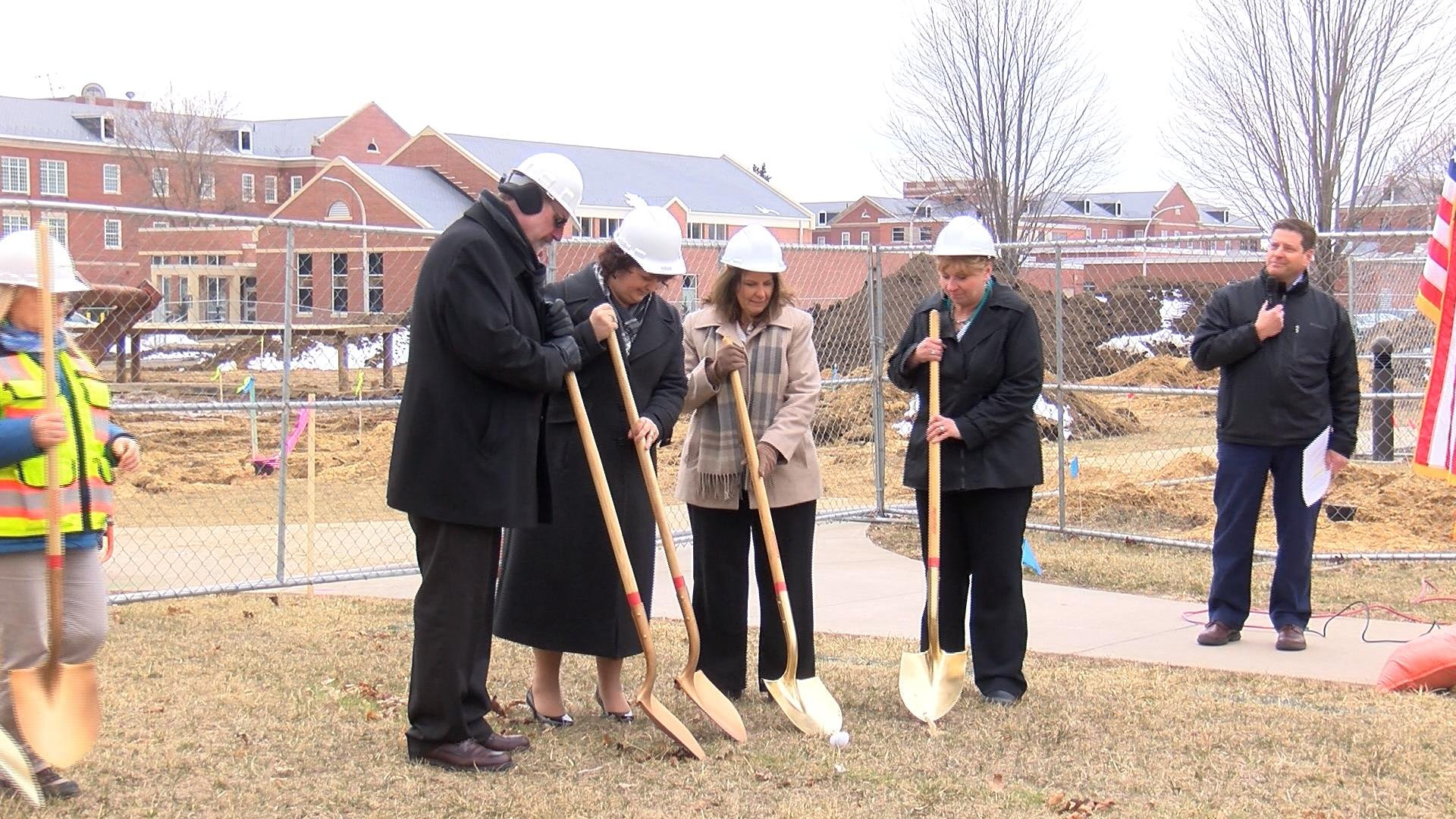 Officials including the Tomah VA Medical Center Director Victoria Brahm dig shovels into the ground for the groundbreaking ceremony.