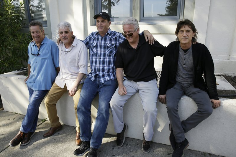 In this Friday, April 13, 2018, photo, the Waldos, from left, Mark Gravitch, Larry Schwartz, Dave Reddix, Jeffrey Noel and Steve Capper sit on a wall they used to frequent at San Rafael High School in San Rafael, Calif. Friday is April 20, or 4/20.