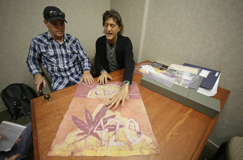 In this Friday, April 13, 2018, photo, Waldos Dave Reddix, left, and Steve Capper look over a 420 flag from 1972 made by a classmate that is kept at a bank vault in San Francisco. Friday is April 20, or 4/20.