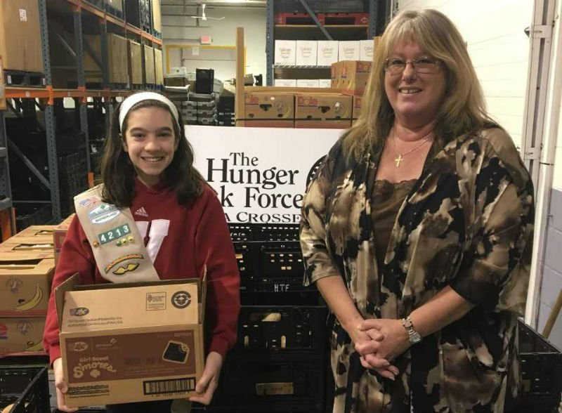 Devan Hutson of La Crosse Cadette Girl Scout Troop 4213 delivers her troop's cookie donation to the Hunger Task Force of La Crosse. Each box donated to a food pantry was matched w/a 1/2-gallon of milk, provided by the La Crosse Co. Dairy Promotion Comm.
