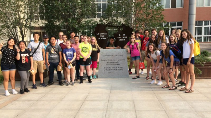 A photo of La Crosse students (left), Chinese students (right) and Principal Bai Fan on the campus of Foreign Language School Number 2, posing beside a plaque commemorating two decades of friendship between La Crosse and Luoyang. (Contributed Photo)