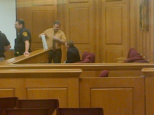 Eric Koula, seated, talking with one of his defense attorneys, Keith Belzer