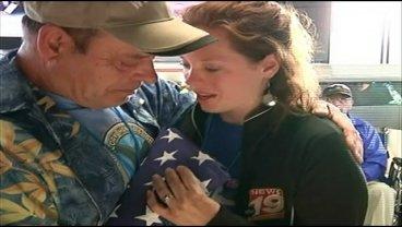 Amy DuPont presents a flag flown over the USS Arizona to Cotter Schaitel, Mark Schaitel's cousin