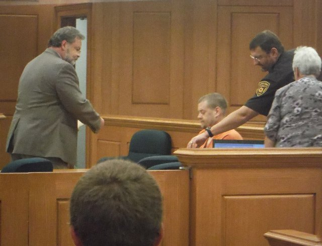 Thomson signs bond paperwork following his hearing Wednesday.