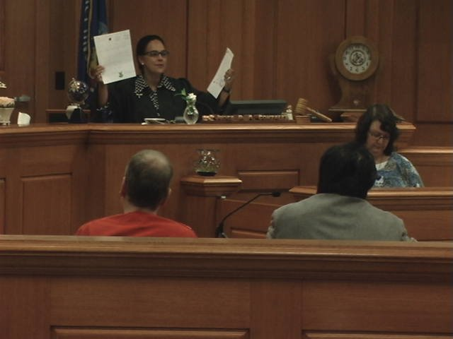 Judge Ramona Gonzalez holds up letters submitted by Petras family members during sentencing