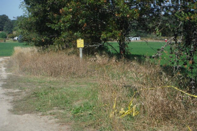 Crime scene tape lays in the grass at the driveway entrance to the Helgeson farm.