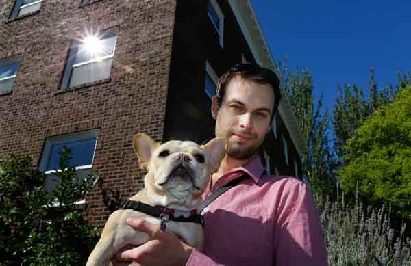 Aaron Brethorst poses while walking his dog, Moxie, in Seattle. He says he'll be able to afford quality insurance and expects better coverage once the Affordable Care Act kicks in. (AP Photo/Ted S. Warren)