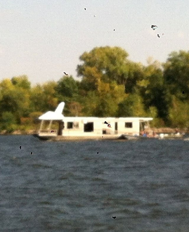 Photo of the houseboat as its removed from where it sank in May.  Photo contributed by Zach Kimmel