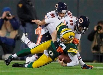 (AP Photo/Jeffrey Phelps). Green Bay Packers quarterback Aaron Rodgers is sacked by Chicago Bears' Shea McClellin (99) and Isaiah Frey (31) during the first half of an NFL football game Monday, Nov. 4, 2013, in Green Bay, Wis.