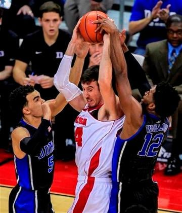 (AP Photo/Andy Manis). Wisconsin's Frank Kaminsky, center, battles between Duke's Tyus Jones, left, Justine Winslow during the first half of an NCAA college basketball game Wednesday, Dec. 3, 2014, in Madison, Wis.
