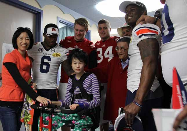 No rivalry today: Wisconsin and Auburn players pose with one of the patients and his family at Tampa General Hospital's Pediatric Unit Saturday afternoon.