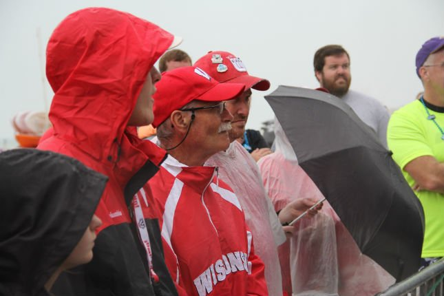 Sporting Badgers colors, fans cover up from the rain at Clearwater Beach and Beach Day for both Wisconsin and Auburn Tuesday
