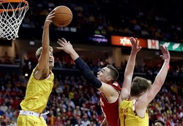 Maryland guard/forward Jake Layman, left, blocks a shot attempt by Wisconsin forward Sam Dekker as he is guarded by Maryland forward Evan Smotrycz, right, in the first half of an NCAA college basketball game, Tuesday, February 24, 2015.