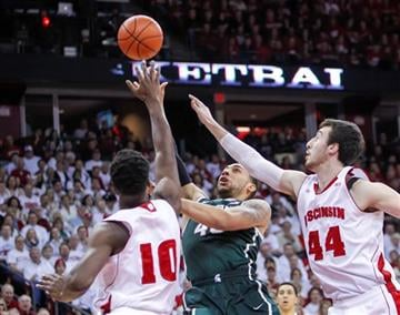 Michigan State's Denzel Valentine, center, shoots between Wisconsin's Nigel Hayes (10) and Frank Kaminsky during the first half of an NCAA college basketball game, Sunday, March 1, 2015, in Madison, Wis.