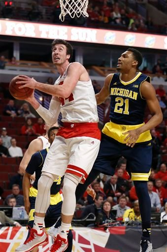 (AP Photo/Kiichiro Sato). Wisconsin's Frank Kaminsky (44) grabs a rebound against Michigan's Zak Irvin (21) in the first half of an NCAA college basketball game in the quarterfinals of the Big Ten Conference tournament,