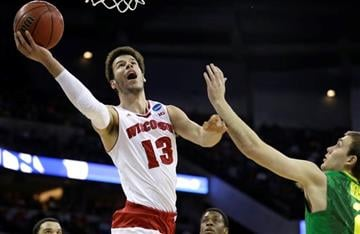 Wisconsin forward Duje Dukan (13) drives to the basket over Oregon guard Casey Benson, right, during the first half of an NCAA college basketball tournament Round of 32 game, Sunday, March 22, 2015, in Omaha, Neb.