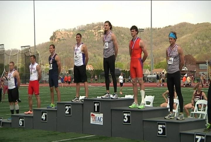 Daniel Otto, center, stands atop the podium after winning the men's 110-meter hurdles Saturday at the WIAC Outdoor Championships.