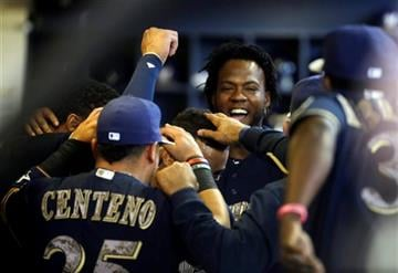 Players congratulate Milwaukee Brewers' Khris Davis in the dugout after umpires originally called him out for not touching home plate after hitting a home run during the first inning Monday.