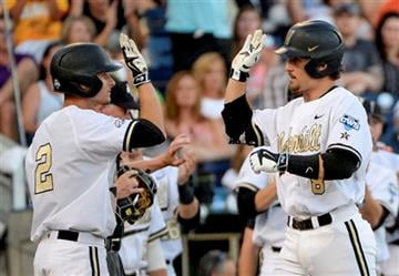 Vanderbilt right fielder Rhett Wiseman, right, celebrates after hitting a two-run home run that scored Tyler Campbell, left, in the fourth inning of an NCAA College World Series baseball game against TCU in Omaha, Neb., Friday, June 19, 2015.