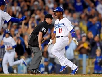 Los Angeles Dodgers' Jimmy Rollins scores on a single by Andre Ethier during the seventh inning of a baseball game against the Milwaukee Brewers, Friday, July 10, 2015, in Los Angeles.
