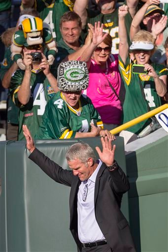 Former Green Bay Packers quarterback Brett Favre waves to fans as he walks onto Lambeau Field prior to getting inducted in to the Packers Hall of Fame and having his No. 4 jersey retired, Saturday, July 18, 2015, in Green Bay.