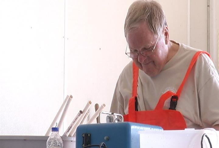 Volunteer Don Schroeder tags fish Tuesday at the Genoa Hatchery