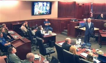 (Colorado Judicial Department via AP, Pool). In this image taken from video, prosecutor George Brauchler, right, gestures to James Holmes, who sits second from left, a picture displayed above showing the twelve victims of the Colorado theater shooting
