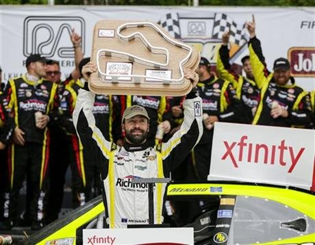Paul Menard holds up the trophy after wining the NASCAR Xfinity Series auto race Saturday, Aug. 29, 2015, at Road America in Elkhart Lake, Wis.