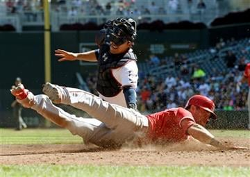 Los Angeles Angels' Taylor Featherston, right, beats the tag by Minnesota Twins catcher Kurt Suzuki to score in the sixth inning of Game 1 of a split doubleheader baseball game, Saturday, Sept. 19, 2015, in Minneapolis.