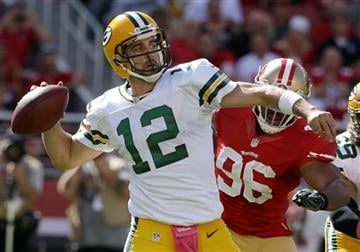 Green Bay Packers quarterback Aaron Rodgers (12) passes as San Francisco 49ers linebacker Corey Lemonier (96) applies pressure during the first half of an NFL football game in Santa Clara, Calif., Sunday, Oct. 4, 2015.