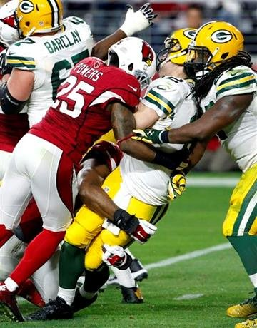 Green Bay Packers quarterback Aaron Rodgers (12) is sacked by Arizona Cardinals cornerback Jerraud Powers (25) during the second half of an NFL football game, Sunday, Dec. 27, 2015, in Glendale, Ariz.