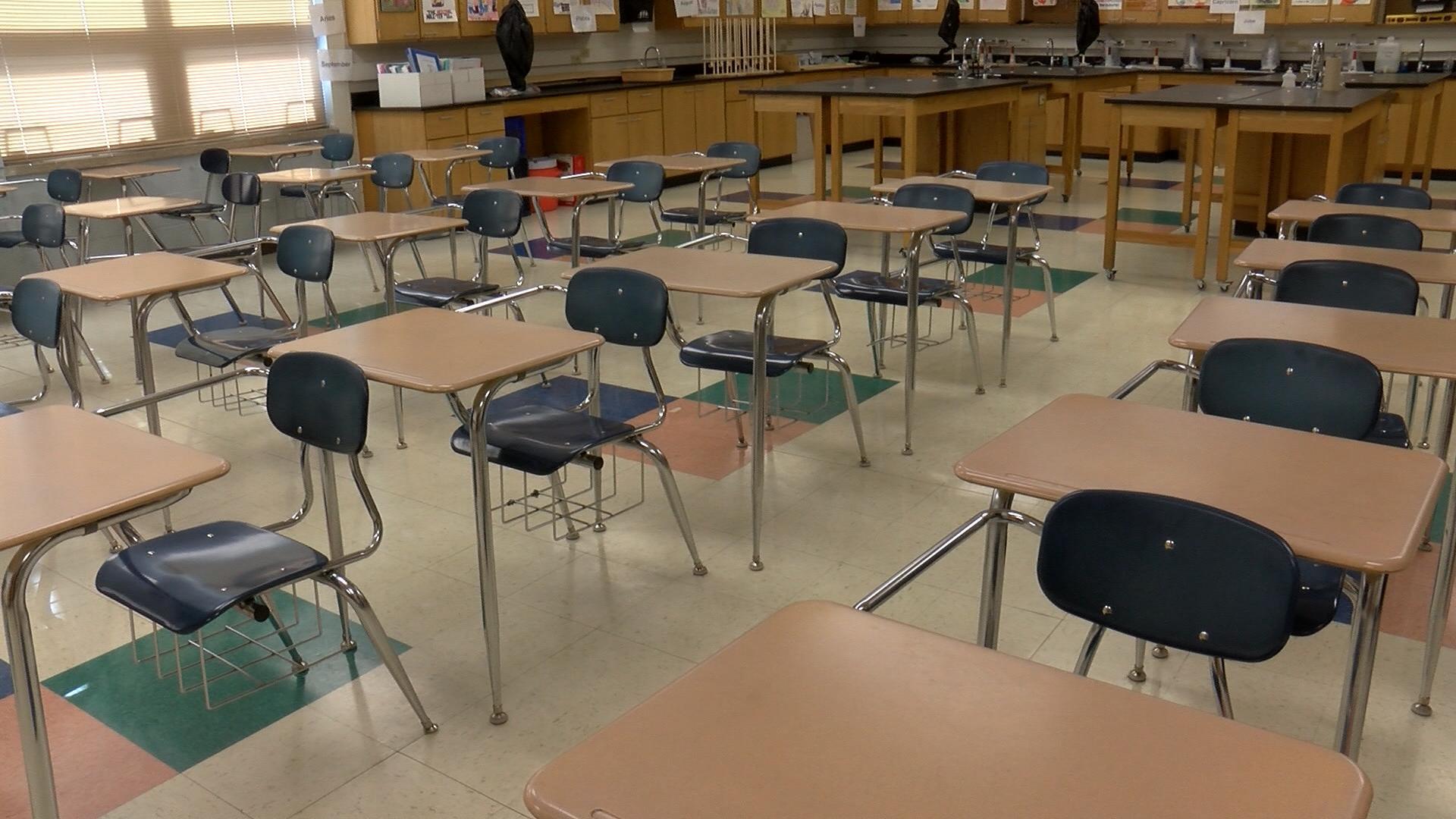 Empty desks fill a classroom.
