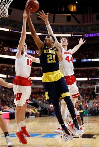 (AP Photo/Charles Rex Arbogast). Michigan's Zak Irvin (21) goes up for a shot against Wisconsin's Sam Dekker (15) and Frank Kaminsky (44) in the first half of an NCAA college basketball game in the quarterfinals of the Big Ten Conference tournament